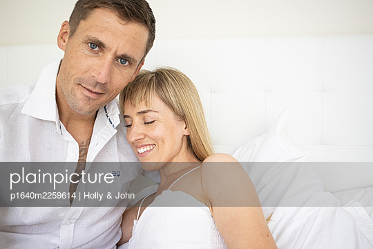 Happy couple sitting on bed, portrait - p1640m2259614 by Holly & John