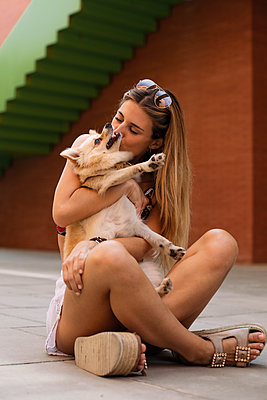 Smiling young woman sitting and kissing her dog - p300m2023752 by Aitor Carrera Porté