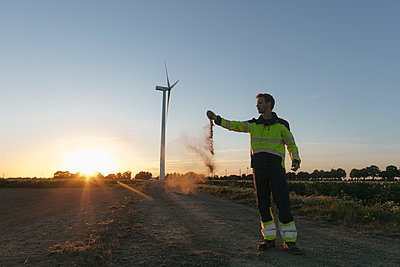 Engineer at a wind turbine at sunset scattering soil - p300m2058835 von Gustafsson