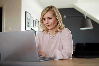 Blond woman using laptop at home - p300m2167489 by Rainer Berg