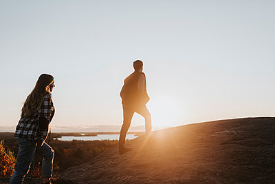 Young couple walking up hill against setting sun - p300m2241222 by Sara Monika