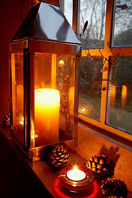 Lit candle on Victorian schoolhouse window with pinecones - p349m789719 by Brent Darby