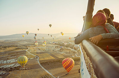 Tourists in hot air balloon basket above field landscape, Cappadocia, Anatolia,Turkey - p429m1022584 by Guido Cavallini