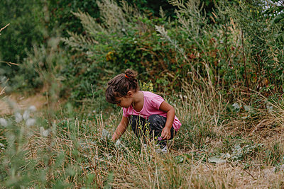 Girl sitting in the middle of the field picking grass - p1166m2213096 by Cavan Images