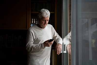 Senior mam using phone while standing by window at home - p300m2242269 by VITTA GALLERY
