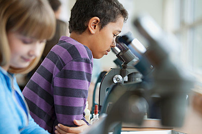 Middle school students using microscopes. - p328m718285f by Hero Images