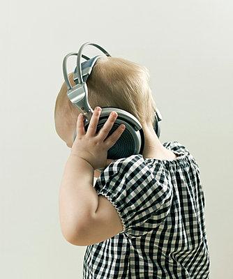 Toddler with headphones - p3882630 by Johannes Romppanen