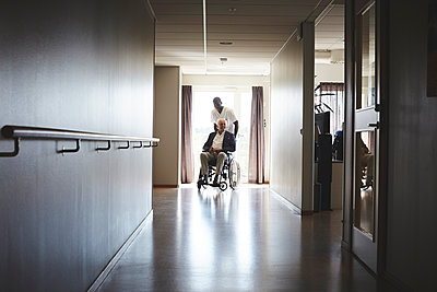 Full length of male nurse pushing senior man on wheelchair at hospital corridor - p426m1494021 by Maskot