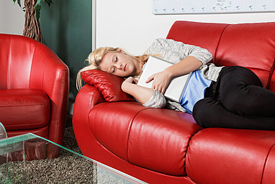 A beautiful young millennial business woman catching a nap on a red couch in a workplace and holding her tablet; Sherwood Park, Alberta, Canada - p442m1580579 by LJM Photo