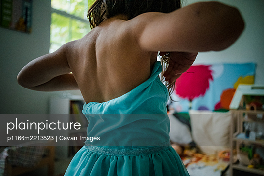 child putting on teal tulle dress - p1166m2213523 by Cavan Images