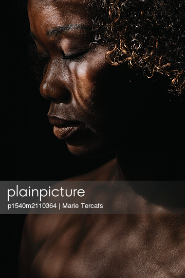 close-up of black woman with shadows of light  - p1540m2110364 by Marie Tercafs