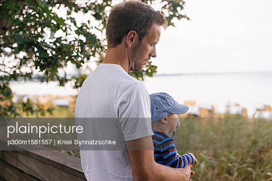Germany, Timmendorfer Strand, father holding his son - p300m1581557 von Kniel Synnatzschke