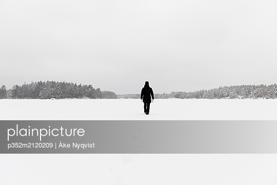Woman wearing black walking on snow covered Stora Skiren lake in Lotorp, Sweden - p352m2120209 by Åke Nyqvist