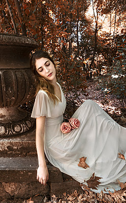 Dreamy young woman in white dress sits on the edge of the woods - p1445m2184798 by Eugenia Kyriakopoulou