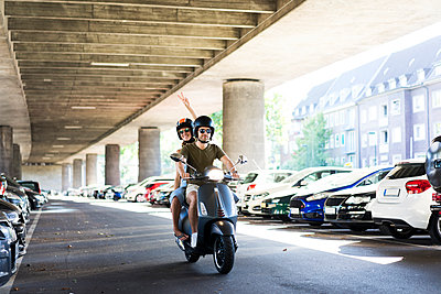 Happy couple riding motor scooter at underpass - p300m2029434 by Joseffson