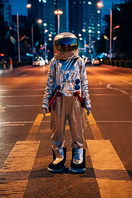 Spaceman standing on a street in the city at night - p300m2043164 by Vasily Pindyurin
