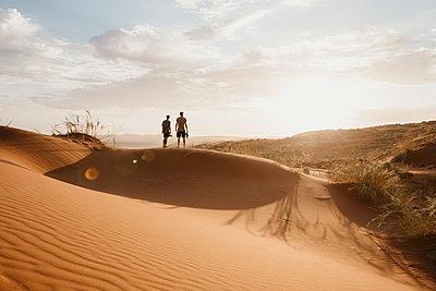 Namibia, Namib desert, Namib-Naukluft National Park, Sossusvlei, two men standing on Elim Dune at sunset - p300m2080845 von letizia haessig photography