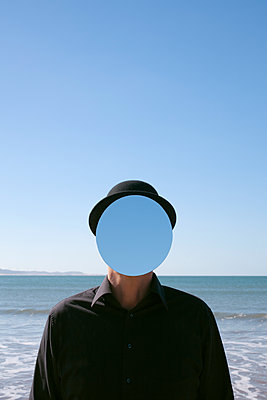 Morocco, Essaouira, man wearing a bowler hat with mirror in front of his face at the sea - p300m2104479 by Petra Stockhausen