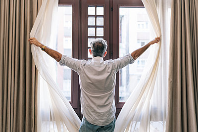 Man opening curtains in hotel room - p300m2250635 by Daniel González