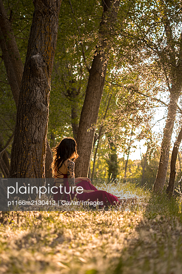 Young woman in a red dress lying in a forest at sunset - p1166m2130413 by Cavan Images