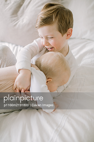 Toddler boy and baby sister playing on bed at home - p1166m2191800 by Cavan Images