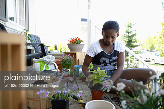 Tween girl potting plants on front stoop - p1192m2000216 by Hero Images