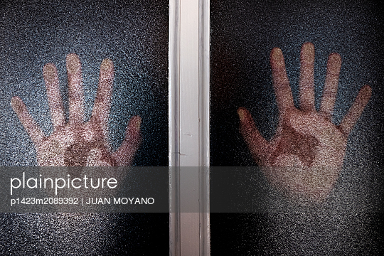 Hands against a translucent glass door or window - p1423m2089392 by JUAN MOYANO