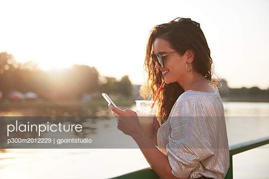 Smiling young woman with cell phone and takeaway drink at the riverside at sunset - p300m2012229 von gpointstudio