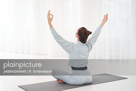 Woman practicing yoga in gym - p430m2244445 by R. Schönebaum