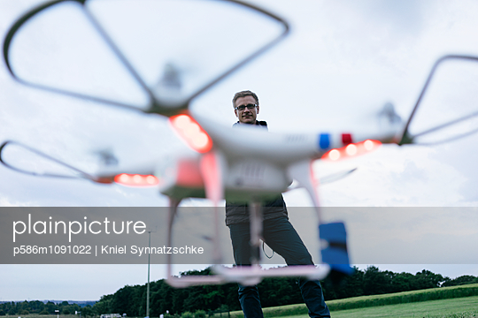 Man operates quadrocopter using remote control - p586m1091022 by Kniel Synnatzschke