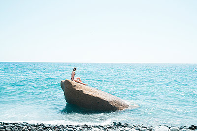 Side view of woman wearing bikini sitting on rock in sea against clear sky during sunny day - p1166m2112087 by Cavan Images