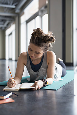 Woman laying on yoga mat writing in journal in gym studio - p1192m1231228 by Hero Images