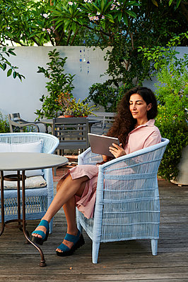 Woman using tablet in garden, portrait - p1640m2254682 by Holly & John