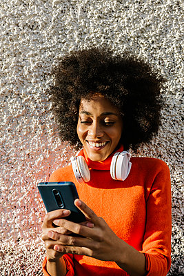 Smiling young woman with headphones using smart phone against textured wall - p300m2256856 by Xavier Lorenzo