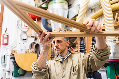 Concentrated male craftsperson looking at triangular wood in workshop - p300m2293669 by Eugenio Marongiu
