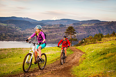 COLUMBIA RIVER GORGE, OR, USA. Two young women ride mountain bikes up a single-track trail with volcano in distance. - p343m1168292 by David Hanson