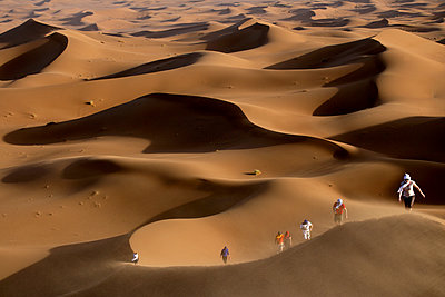 Group of people exploring Erg Chebbi dunes in Sahara Desert - p343m1475893 by David Santiago Garcia
