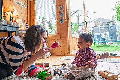 Childminder shaking maraca at baby boy - p429m1469391 by G. Mazzarini