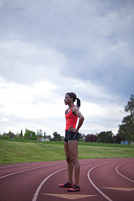Young female sprinter standing in track lane, side view - p4342610f by Alin Dragulin