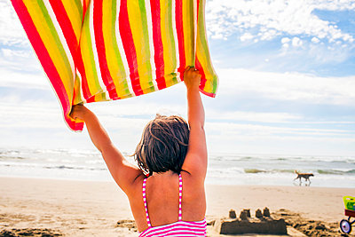 Caucasian woman holding towel in wind on beach - p555m1420531 by Adam Hester
