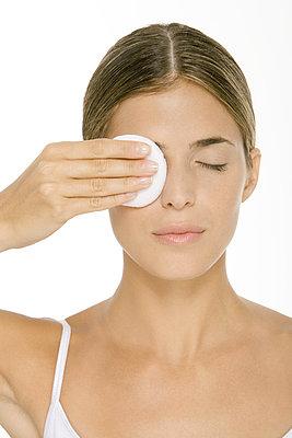 Woman removing eye make-up - p62312650f by Alix Minde
