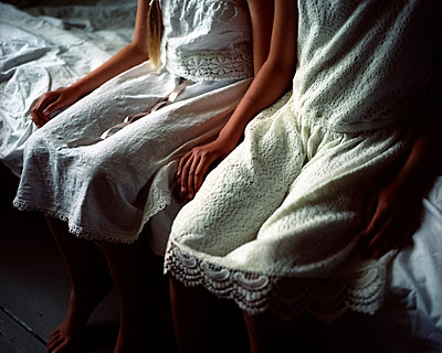Two girls side by side on the edge of the bed - p945m1155033 by aurelia frey