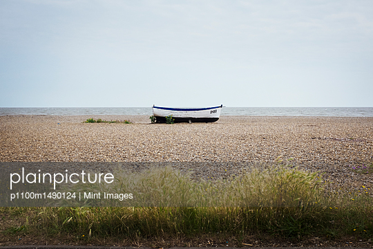 White fishing boat lying mid distance on pebble beach. - p1100m1490124 by Mint Images