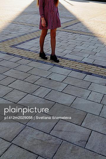 Teenager geht über Gehwegplatten auf einem Platz - p1412m2029058 von Svetlana Shemeleva