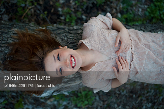 Young woman lying on a tree trunk - p1646m2281175 by Slava Chistyakov