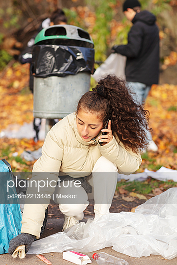 Young female volunteer talking on smart phone while collecting garbage in park - p426m2213448 by Maskot