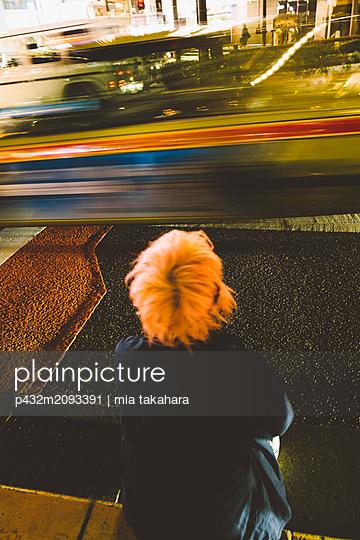 Junger Mann sitzt am Straßenrand - p432m2093391 von mia takahara