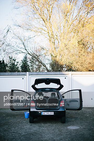 Auto in einem Hinterhof mit offener Heckklappe  - p586m972957 von Kniel Synnatzschke