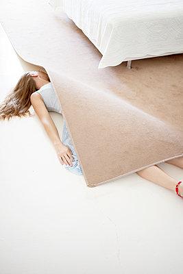 Woman lying under carpet - p1105m2126430 by Virginie Plauchut
