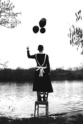 Maid on a chair holding black balloons - p1521m2158323 by Charlotte Zobel